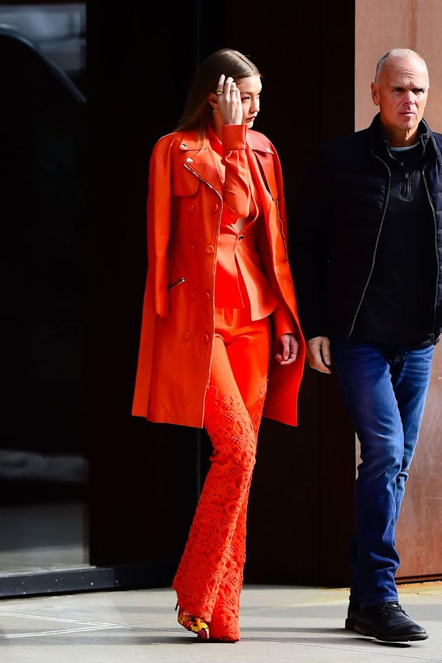 "<p>In a leather <a rel=""nofollow"" href=""https://www.moschino.com/us_en/"">Moschino</a> by Jeremy Scott trench coat, an orange button down top, lace detailed trousers, and floral pumps while out in NYC. </p>"