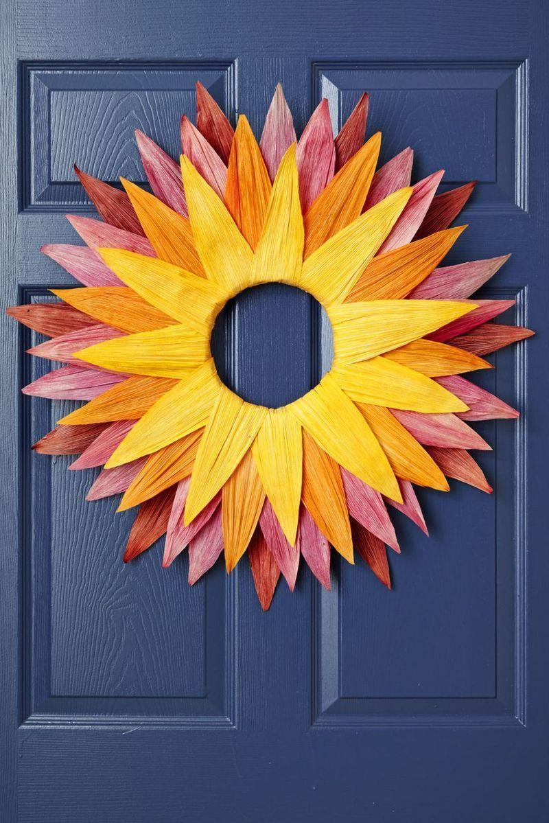 """<p>A pretty collection of yellows, oranges, pinks, and reds makes this wreath a perfect fit for the fall season—but we think it'd still look appropriate on your front porch come spring and summer. </p><p><strong>Make the wreath:</strong> Set four medium plastic bins on a covered surface. In each, mix 6 cups of warm water, 3 Tbsp vinegar, and 1 cup Rit liquid fabric dye in desired colors. <strong>Note:</strong> Wear gloves so your hands don't get stained from the dye. Soak dried corn husk in the mixture for 20 minutes; rinse with water and let dry on newspaper. Place husks between two thin towels and iron flat. Hot-glue a few layers of dyed corn husks around a 12"""" foam wreath form to create a sunburst shape. Attach a loop of wire to the back with hot glue and use to hang. </p>"""