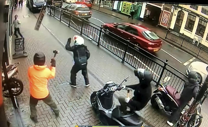 The moment the salon worker threw the shop sign at the gang. (SWNS)