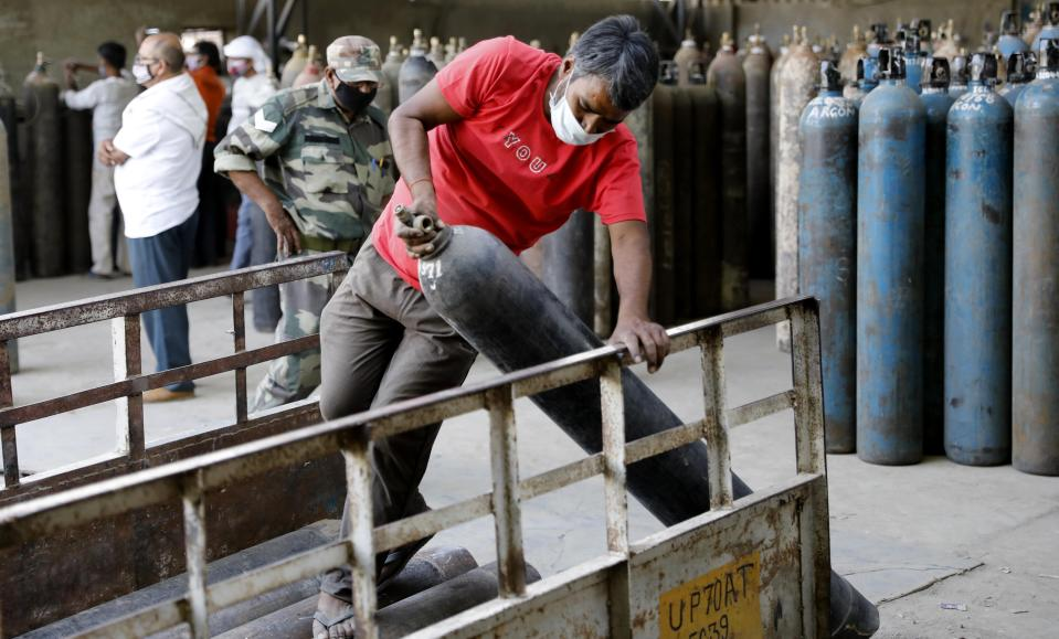 Workers load oxygen cylinders at a charging station on the outskirts of Prayagraj, India, Friday, April 23, 2021. India put oxygen tankers on special express trains as major hospitals in New Delhi on Friday begged on social media for more supplies to save COVID-19 patients who are struggling to breathe. India's underfunded health system is tattering as the world's worst coronavirus surge wears out the nation, which set another global record in daily infections for a second straight day with 332,730. (AP Photo/Rajesh Kumar Singh)