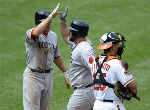 Boston Red Sox's Kelly Shoppach, center, celebrates his two-run home run with teammate Scott Podsednik, left, as Baltimore Orioles catcher Luis Exposito, right, looks on during the sixth inning of a baseball game, Wednesday, May 23, 2012, in Baltimore. The Red Sox won 6-5. (AP Photo/Nick Wass)