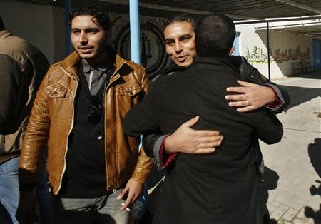 A Palestinian man is hugged by a relative after he was freed from a Hamas-run jail in Gaza City January 8, 2014. REUTERS/Suhaib Salem