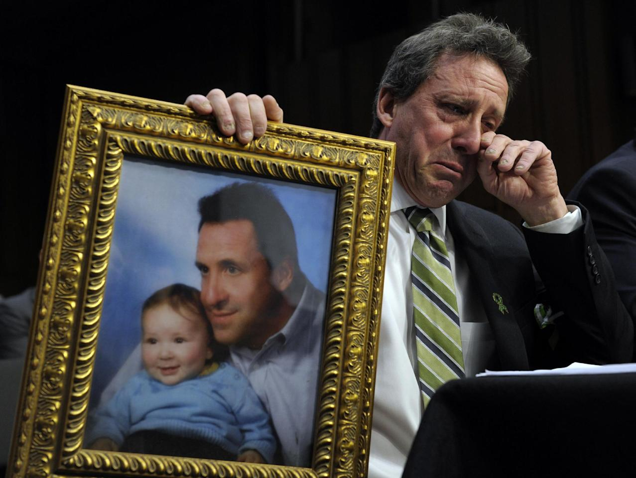 Neil Heslin, the father of a six-year-old boy who was slain in the Sandy Hook massacre in Newtown, Conn., on Dec. 14, holds a picture of himself with his son Jesse and wipes his eye while testifying on Capitol Hill in Washington, Wednesday, Feb. 27, 2013, before the Senate Judiciary Committee on the Assault Weapons Ban of 2013. (AP Photo/Susan Walsh)