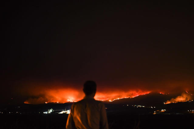<p>A man stands by the roadside as he watches a wildfire burn in the distance at Anciao, Leiria, central Portugal, June 18, 2017. (Patricia De Melo Moreira/AFP/Getty Images) </p>