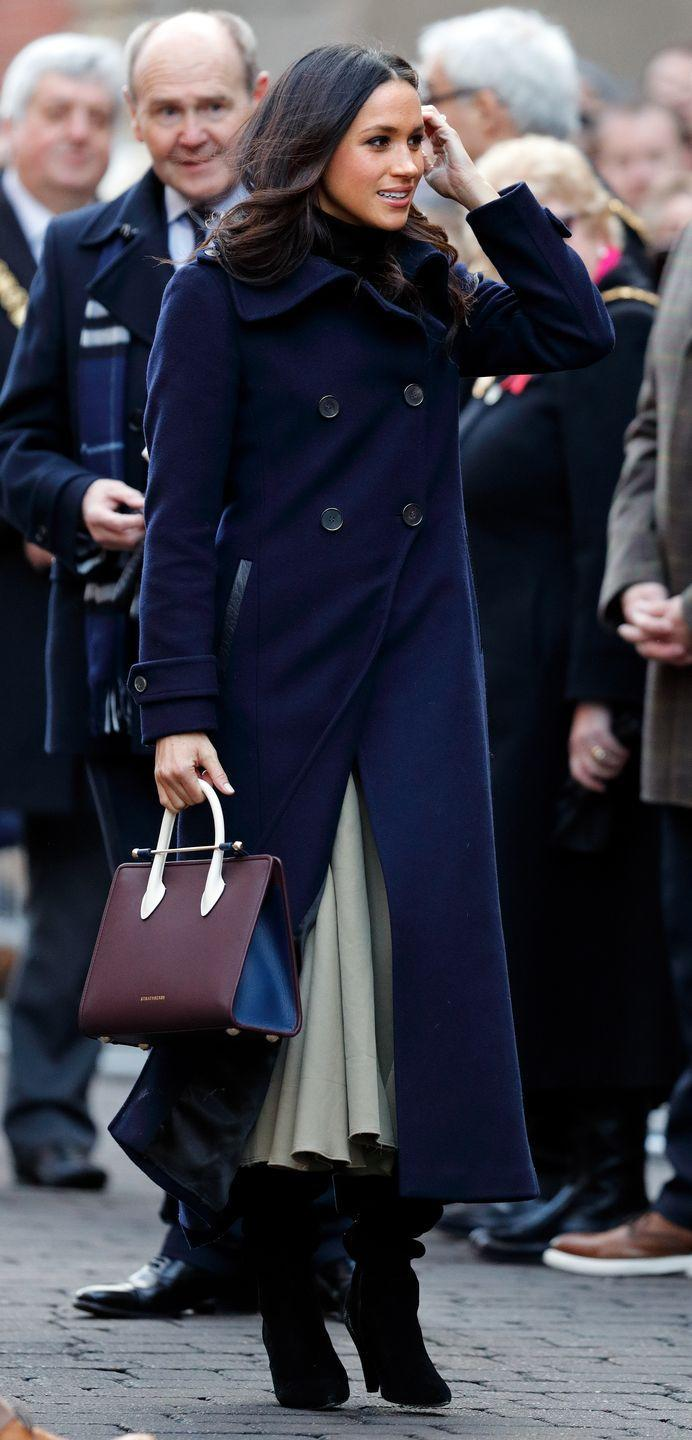<p>Meghan attended her first public appearance with Prince Harry in Nottingham wearing an all-British/Amercian fashion ensemble comprising of a double-breasted Mackage navy coat, Joseph skirt and carried a burgundy and navy blue Strathberry handbag. </p>