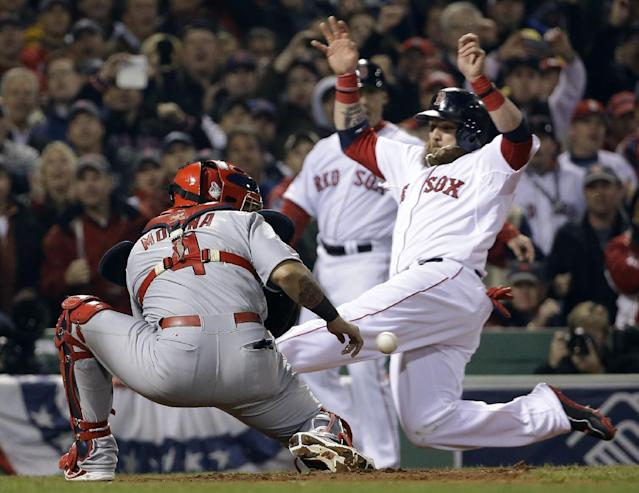 Boston Red Sox's Jonny Gomes slides safely past St. Louis Cardinals catcher Yadier Molina during the third inning of Game 6 of baseball's World Series Wednesday, Oct. 30, 2013, in Boston. Gomes scored from first on a double by Shane Victorino. (AP Photo/David J. Phillip)