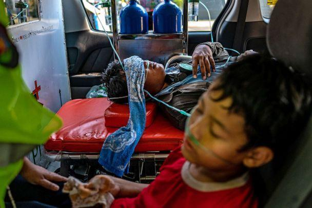 PHOTO: An anti-coup protester and a child who were exposed to tear gas receive oxygen from medics on March 1, 2021 in Yangon, Myanmar. Myanmar's military government has recently intensified a crackdown on protesters, using tear gas and live ammunition. (Hkun Lat/Getty Images, FILE)