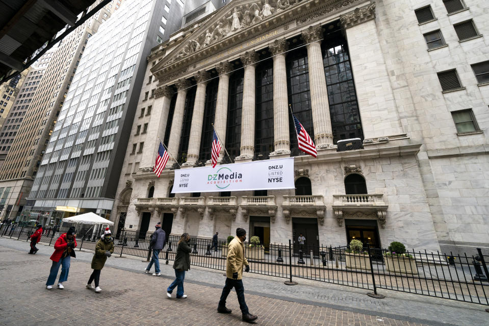 Pedestrians pass the New York Stock Exchange, Wednesday, Jan. 27, 2021, in New York. Major indexes opened lower on Wall Street Friday, Jan. 29, while shares of GameStop, AMC and several other stocks being targeted by a rowdy community of amateur investors soared again. (AP Photo/John Minchillo)
