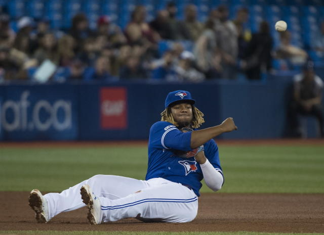 Toronto Blue Jays third baseman Vladimir Guerrero Jr. (27) makes a throw to first base to throw out Boston Red Sox's Rafael Devers during the fourth inning of a baseball game in Toronto on Thursday, May 23, 2019. (Nathan Denette/The Canadian Press via AP)