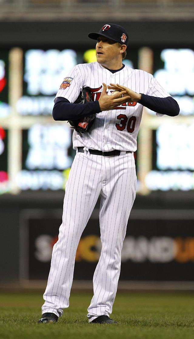 Minnesota Twins starting pitcher Kevin Correia roughs up the ball after giving up a double to Detroit Tigers' Austin Jackson during the third inning of a baseball game in Minneapolis, Friday, April 25, 2014. (AP Photo/Ann Heisenfelt)