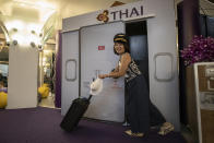 A woman takes a souvenir photo in a flight-themed restaurant at the Thai Airways head office in Bangkok, Thailand on Oct. 3, 2020. The airline is selling time on its flight simulators to wannabe pilots while its catering division is serving meals in a flight-themed restaurant complete with airline seats and attentive cabin crew. The airline is trying to boost staff morale, polish its image and bring in a few pennies, even as it juggles preparing to resume international flights while devising a business reorganization plan. (AP Photo/Sakchai Lalit)