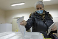 A woman casts her ballot for the local elections at a polling station in Mostar, Bosnia, Sunday, Dec. 20, 2020. Divided between Muslim Bosniaks and Catholic Croats, who fought fiercely for control over the city during the 1990s conflict, Mostar has not held a local poll since 2008, when Bosnia's constitutional court declared its election rules to be discriminatory and ordered that they be changed. (AP Photo/Kemal Softic)