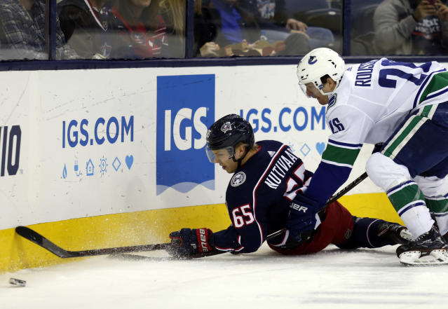 Columbus Blue Jackets defenseman Markus Nutivaara, left, of Finland, passes the puck against Vancouver Canucks forward Antoine Roussel, of France, during the first period of an NHL hockey game in Columbus, Ohio, Tuesday, Dec. 11, 2018. (AP Photo/Paul Vernon)