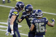 Seattle Seahawks tight end Jacob Hollister (86), left, celebrates with quarterback Russell Wilson (3) and wide receiver Tyler Lockett (16) after Hollister caught a pass from Wilson for a touchdown during the second half of an NFL football game, Sunday, Dec. 27, 2020, in Seattle. The Seahawks won 20-9. (AP Photo/Elaine Thompson)