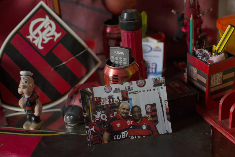 In this April 28, 2014 photo, a printed photograph showing Maria Boreth de Souza, alias Zica, and her husband Carltioel Moraes, both wearing Flamengo soccer jerseys, sits in Souza's home alongside Flamengo soccer memorabilia at her home in the Olaria neighborhood of Rio de Janeiro, Brazil. Souza met her husband during a Flamengo game. (AP Photo/Leo Correa)
