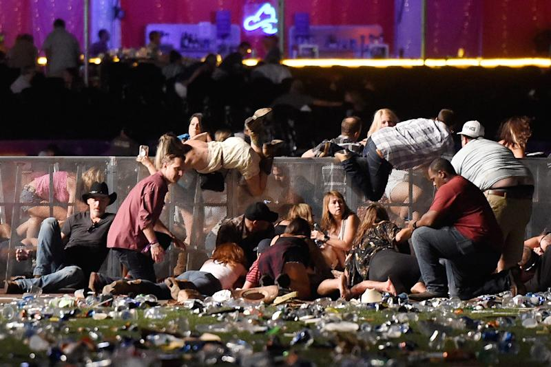 People scramble for shelter at the Route 91 Harvest country music festival after gunfire was heard on Oct. 1, 2017, in Las Vegas.