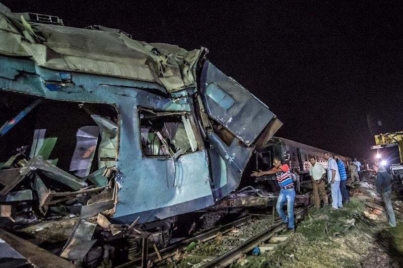 Emergency personnel and Egyptian military police search the wreckage of the train collision on August 11, 2017 near Khorshid station in Alexandria