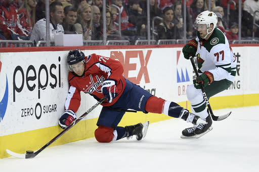 Washington Capitals center Travis Boyd (72) crashes into the boards next to Minnesota Wild defenseman Brad Hunt (77) during the second period of an NHL hockey game Friday, March 22, 2019, in Washington. (AP Photo/Nick Wass)