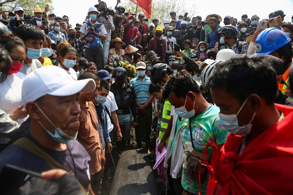 <p>People gather around the coffin of Ma Kyal Sin during her funeral in Mandalay, Myanmar on 4 March. The teenager, who was wearing the T-shirt 'Everything will be ok' was killed during the violence on Wednesday</p> (EPA)