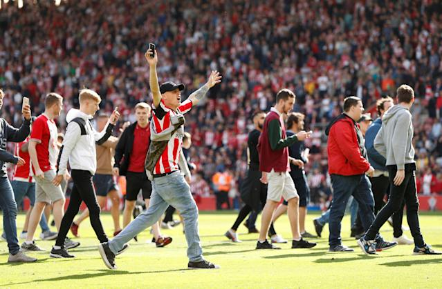 "Soccer Football - Premier League - Southampton vs Manchester City - St Mary's Stadium, Southampton, Britain - May 13, 2018 Southampton fans invade the pitch after the match Action Images via Reuters/John Sibley EDITORIAL USE ONLY. No use with unauthorized audio, video, data, fixture lists, club/league logos or ""live"" services. Online in-match use limited to 75 images, no video emulation. No use in betting, games or single club/league/player publications. Please contact your account representative for further details."