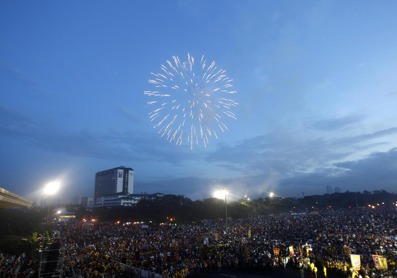 Fireworks light up the sky during a dawn mass at the Rizal Park Monday Jan. 9, 2012 to celebrate the feast of the Black Nazarene in Manila, Philippines. More than 3 million devotees paraded the charred Christ statue, believed to have healing powers, through the Philippine capital despite a warning from President Benigno Aquino III that terrorists might target the gathering. (AP Photo/Bullit Marquez)
