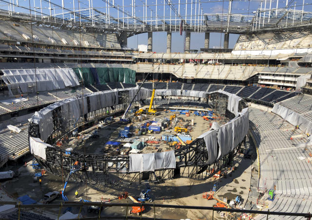 In this Jan. 22, 2020, file photo, works continues on the interior of SoFi Stadium and preparing to raise the circular Oculus video board in Inglewood, Calif. The opening of the stadium on Sept. 13 has the Los Angeles Rams hosting the Dallas Cowboys in an NFL football game. (AP Photo/Greg Beacham, File)