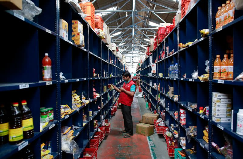 An employee scans a package for an order at a Big Basket warehouse on the outskirts of Mumbai