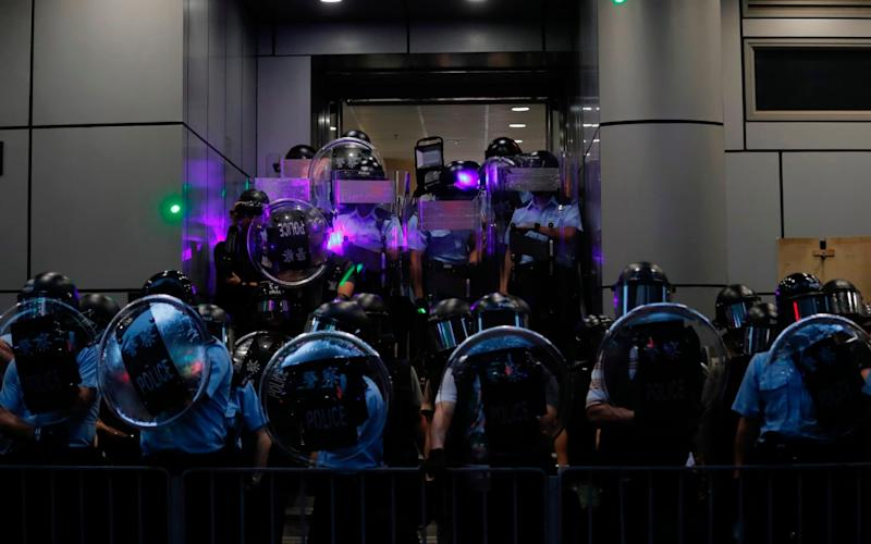 Police officers armed with riots gear stand outside Mong Kok police station during pro-democracy protesters march in Hong Kong on Saturday - AP