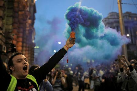 A protester lights a flare during a protest against Prime Minister Aleksandar Vucic's government in Belgrade
