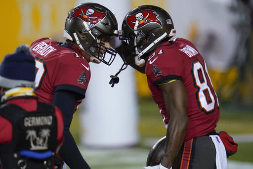 Tampa Bay Buccaneers quarterback Tom Brady (12) and wide receiver Antonio Brown (81) celebrating a touchdown pass during the first half of an NFL wild-card playoff football game against the Washington Football Team, Saturday, Jan. 9, 2021, in Landover, Md. (AP Photo/Julio Cortez)