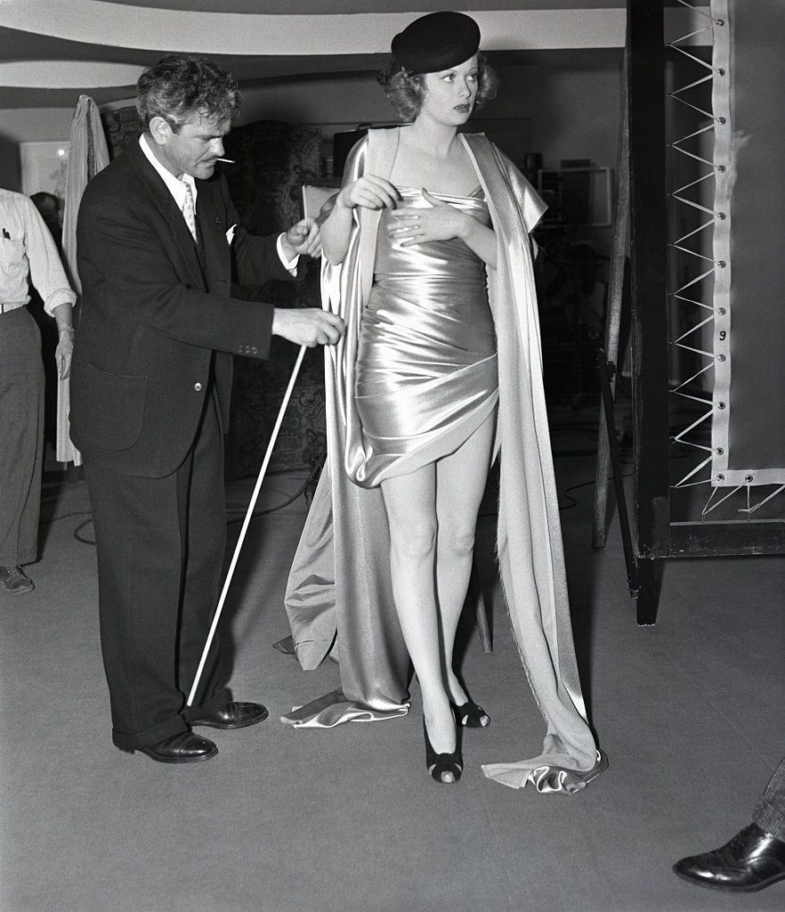 <p>The director of <em>Beauty For the Asking</em> makes sure Lucille's outfit is perfect before shooting a scene for the movie, in which the actress portrayed a model.</p>