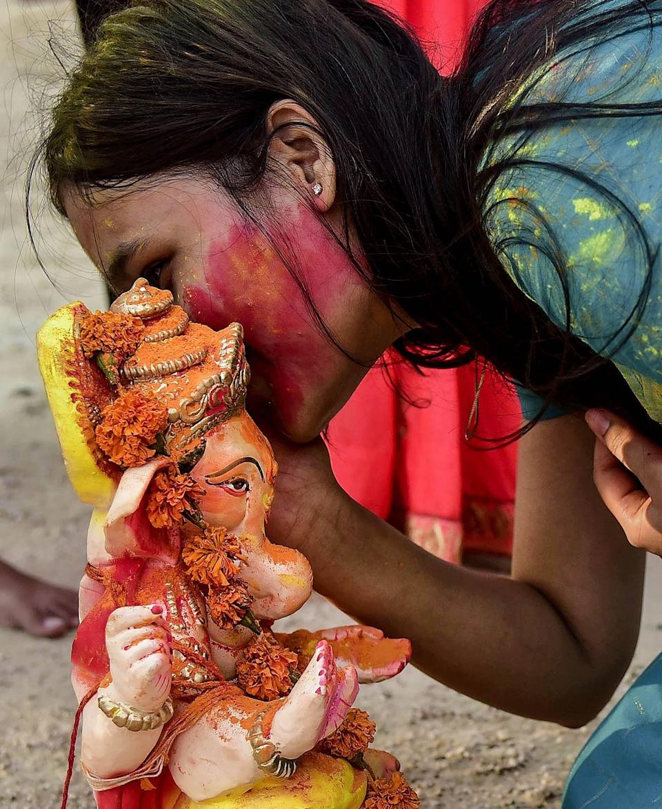 A devotee with an idol of Lord Ganesha before its immersion in a pond during Ganesh Chaturthi celebrations, in Bikaner. (PTI photo)