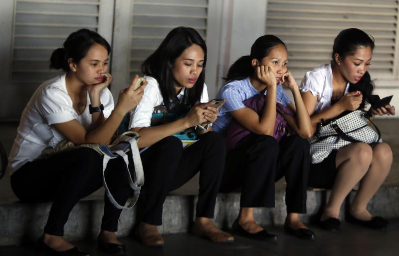 Job applicants of a supermarket sit on a pavement as they wait for their turn to be interviewed in Paranaque, Metro Manila