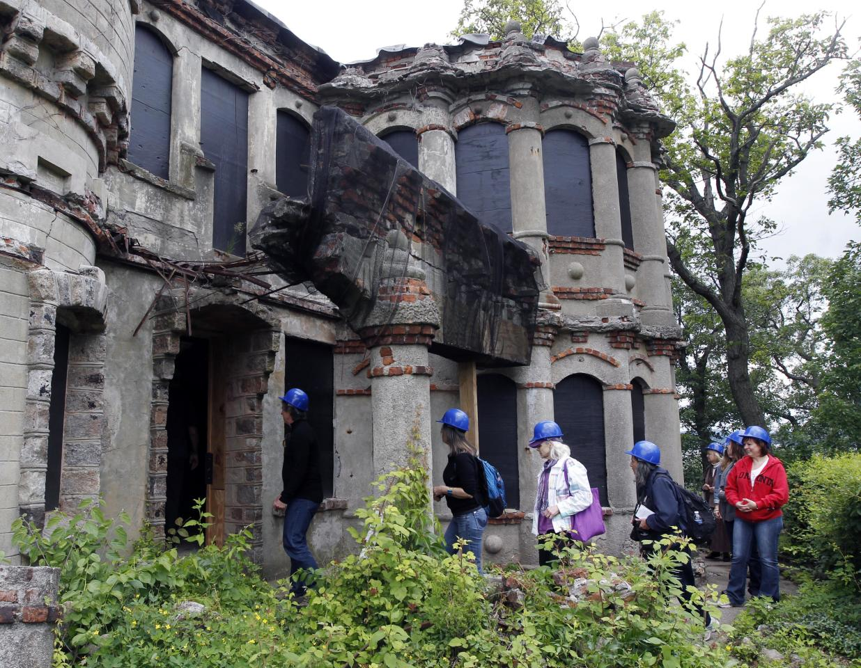 Media and tourism officials enter the Bannerman residence during a tour of the Bannerman Castle on Pollepel Island, N.Y., on Tuesday, June 5, 2012. Though it looks like it was built to withstand battering rams, it was actually a surplus military goods warehouse made to resemble a Scottish castle. Businessman Francis Bannerman VI had it built early in the 20th century as a place to store helmets, haversacks, mess kits and munitions he could not store in his thriving shop in Manhattan. (AP Photo/Mike Groll)