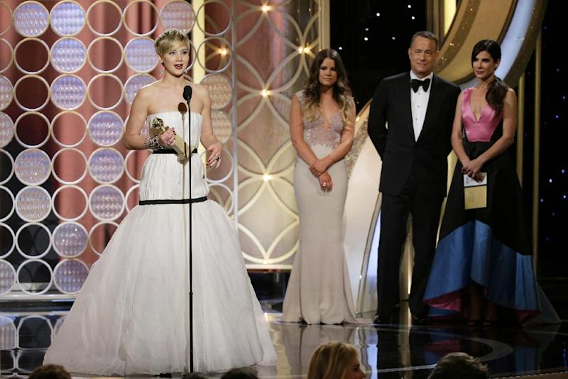 "This image released by NBC shows Jennifer Lawrence, left, accepting the award for best supporting actress in a motion picture for her role in ""American Hustle,"" as presenters Sandra Bullock, right, and Tom Hanks, second right, look on during the 71st annual Golden Globe Awards at the Beverly Hilton Hotel on Sunday, Jan. 12, 2014, in Beverly Hills, Calif. (AP Photo/NBC, Paul Drinkwater)"