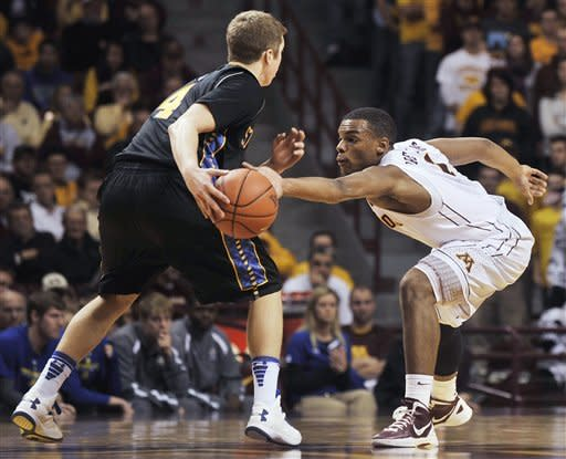 Minnesota's Andre Hollins, right, attempts to steal the ball from South Dakota State's Jake Bittle during the second half of an NCAA college basketball game, Tuesday, Dec. 4, 2012, in Minneapolis. Minnesota won 88-64. (AP Photo/Tom Olmscheid)