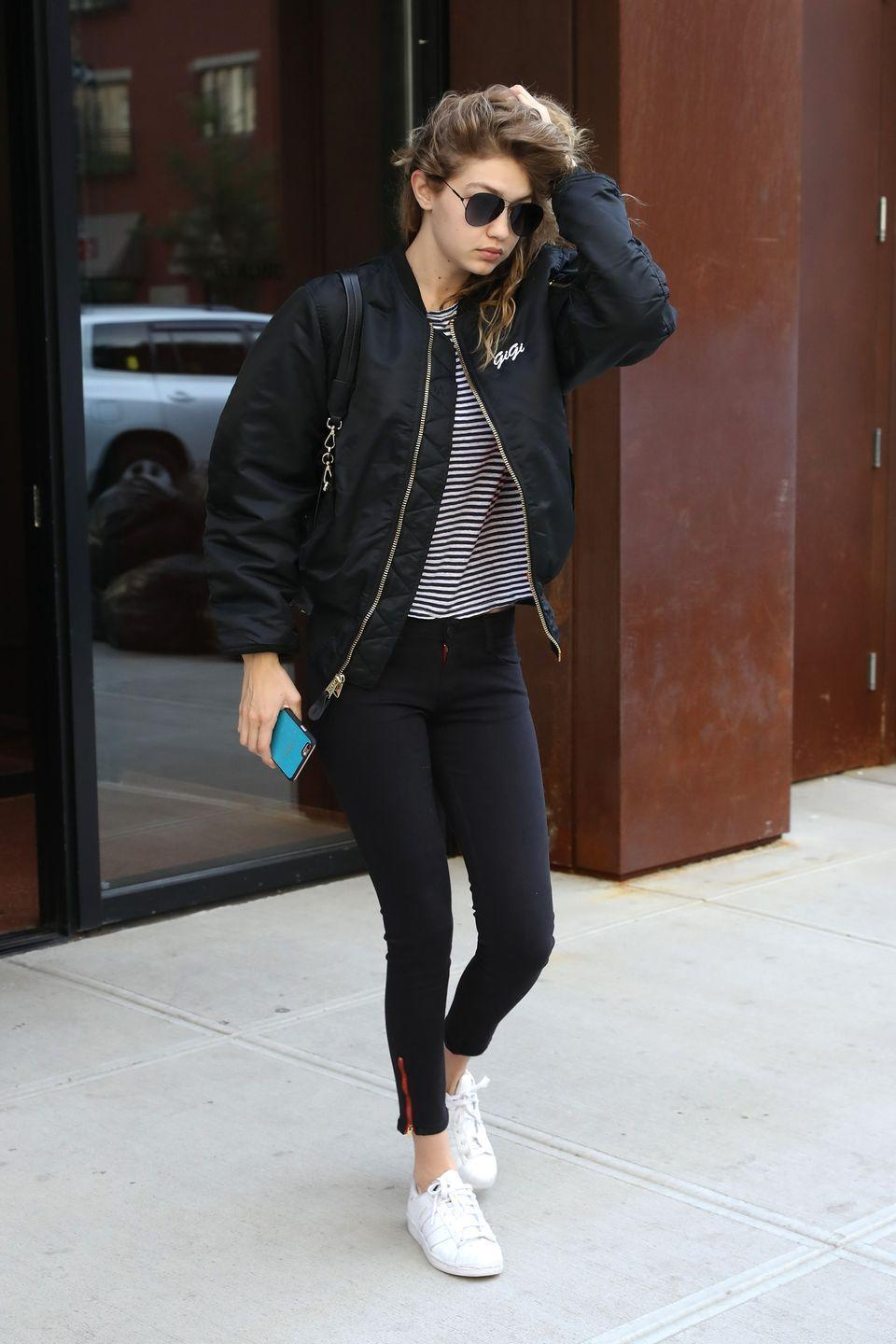 """<p>Hadid rocks her go-to athleisure look with a personalized black bomber jacket featuring a small """"Gigi"""" logo on the chest</p>"""