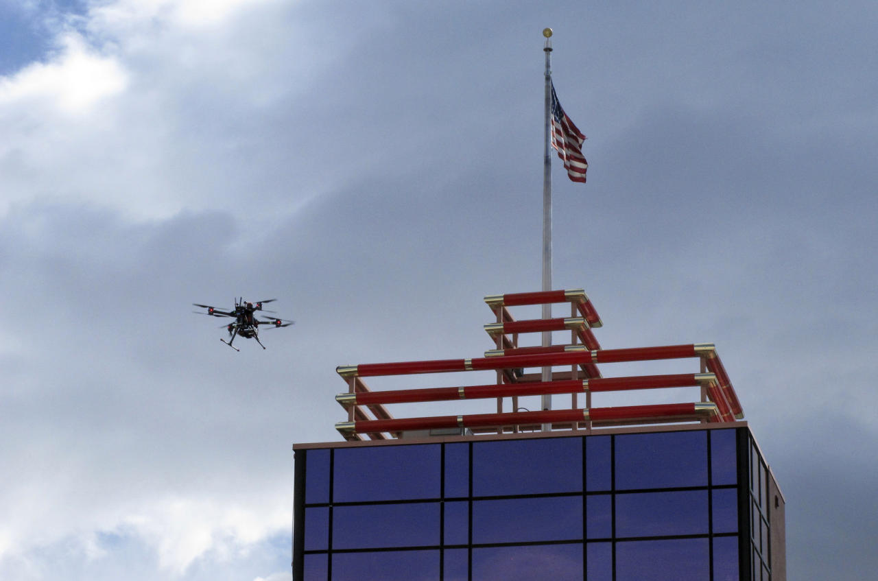 In this Tuesday, May 21, 2019 photo, a drone flies over downtown Reno, Nev., before landing on the Cal-Neva casino parking garage, as part of a NASA simulation to test emerging technology that someday will be used to manage travel of hundreds of thousands of commercial, unmanned aerial vehicles (UAVs) delivering packages. It marked the first time such tests have been conducted in an urban setting. (AP Photo/Scott Sonner)