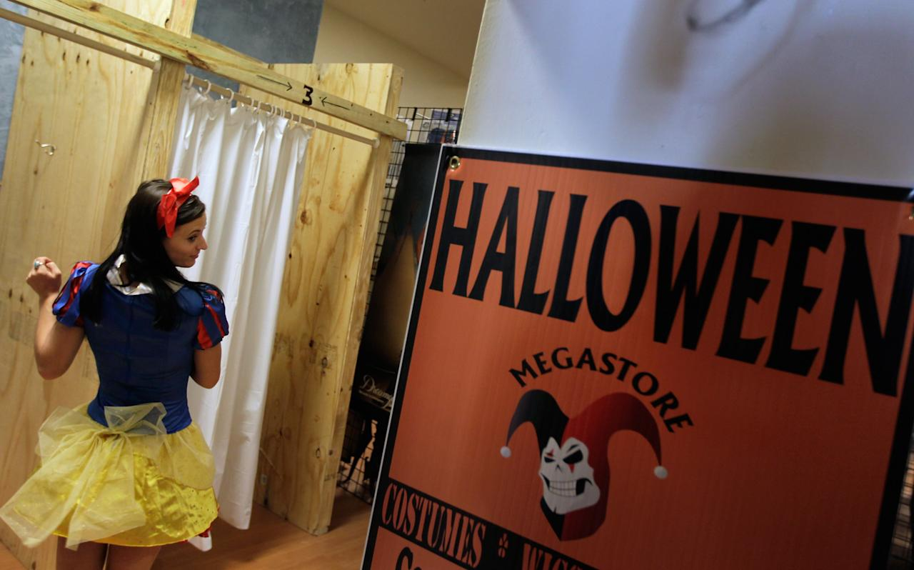 MIAMI BEACH, FL - OCTOBER 21: Charlie Lucas tries on a snow white Costume at the Halloween MegaStore Miami Beach  on October 21, 2011 in Miami Beach, Florida. The megastore is a temporary location for the store which opened for the holiday to sell costumes, masks and other items to people needing to dress up for the evening of October 31 when costumed people around the world observe the day.  (Photo by Joe Raedle/Getty Images)