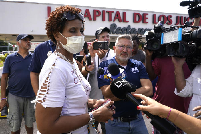 Angelica Green talks with the news media near the scene of a shooting outside a banquet hall near Hialeah, Fla., Sunday, May 30, 2021. Two people died and an estimated 20 to 25 people were injured in a shooting outside a banquet hall in South Florida, police said. The gunfire erupted early Sunday at the El Mula Banquet Hall in northwest Miami-Dade County, near Hialeah, police told news outlets. Green said her son and nephew were injured in the shooting. (AP Photo/Lynne Sladky)