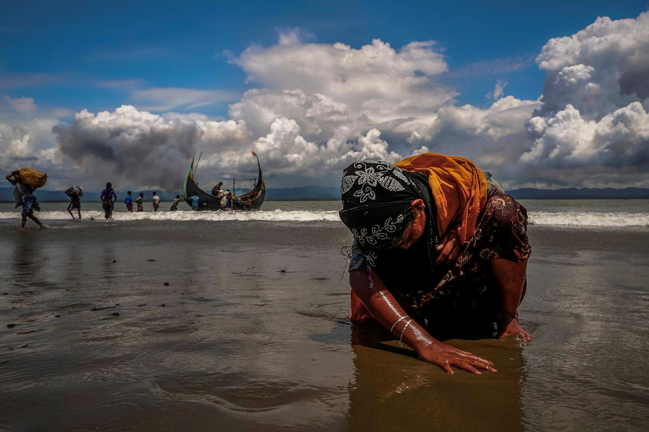 <p>An exhausted Rohingya refugee woman touches the shore after crossing the Bangladesh-Myanmar border by boat through the Bay of Bengal, in Shah Porir Dwip, Bangladesh, Sept. 11, 2017. (Photo: Danish Siddiqui/Reuters) </p>