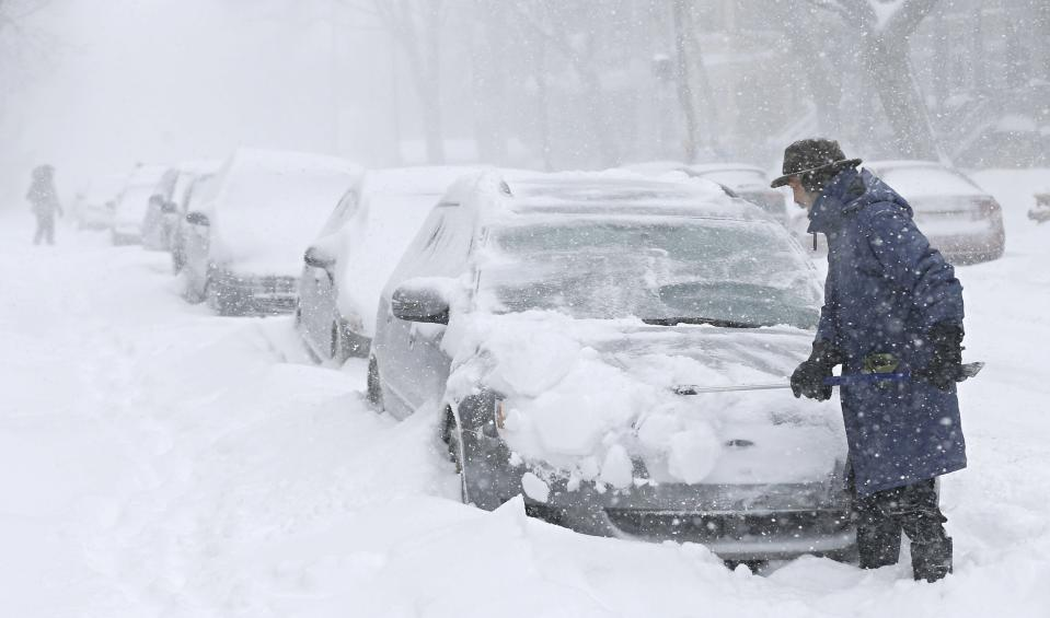 A man clears snow from his car during a snowstorm in Quebec City, December 15, 2013. (Reuters)