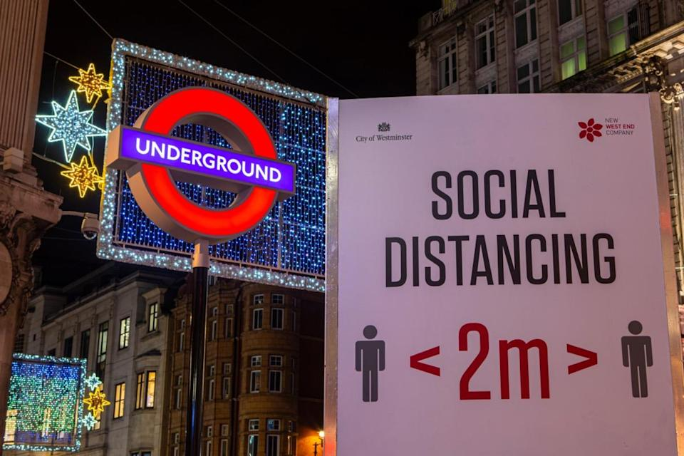 A social distancing sign, pictured next to the London Underground sign at Oxford Circus Station in London, UK.