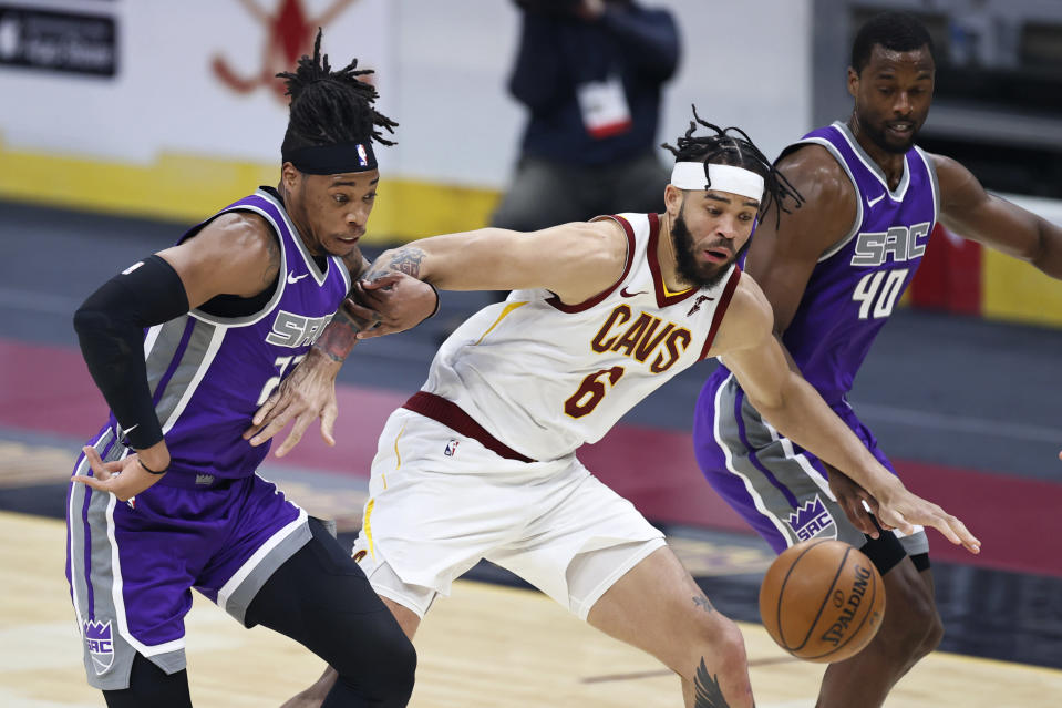 Cleveland Cavaliers' JaVale McGee (6) works between Sacramento Kings' Richaun Holmes (22) and Harrison Barnes (40) for the ball during the first half of an NBA basketball game Monday, March 22, 2021, in Cleveland. (AP Photo/Ron Schwane)