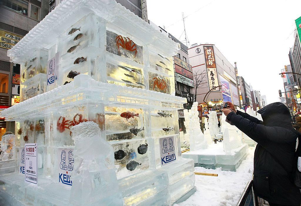 A man takes a photo of an ice sculpture with real fish frozen inside during the 60th Sapporo Snow Festival in Sapporo, Japan.