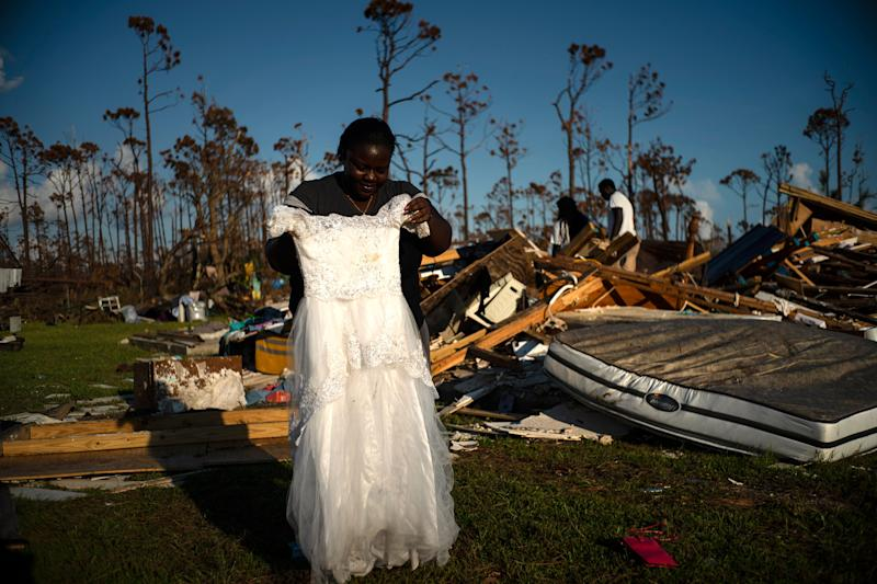 Synobia Reckley holds up the dress her niece wore as a flower girl at her wedding, as she goes through valuables in the rubble of her home destroyed one week ago by Hurricane Dorian in Rocky Creek East End, Grand Bahama, Bahamas, Sept. 8, 2019. | Ramon Espinosa—AP