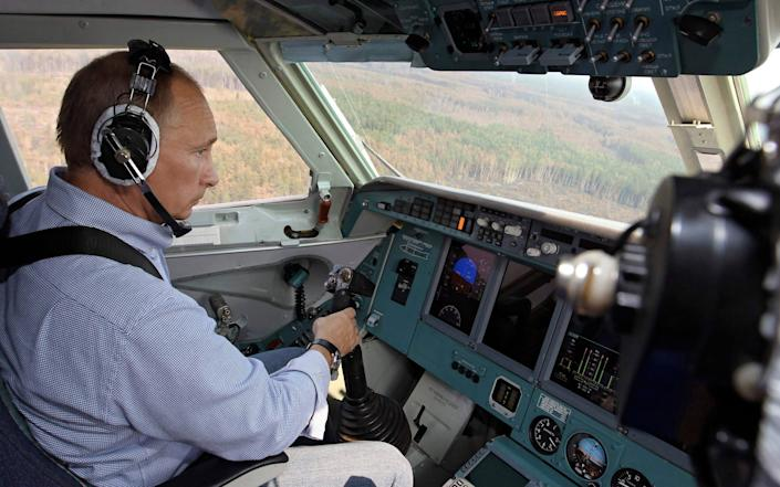 Russia's Prime Minister Vladimir Putin, wearing headphones, sits in the cockpit of a firefighting plane - Ria Novosti/Reuters