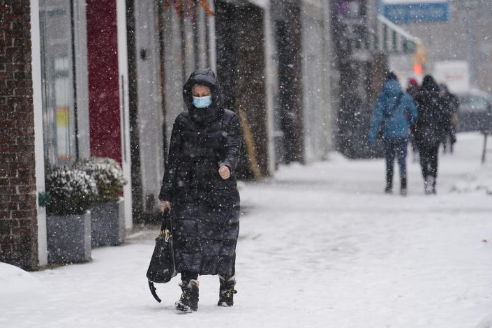 Pedestrians wear protective masks during the coronavirus pandemic as they walk along 71st Avenue as snow falls Thursday, Feb. 18, 2021, in the Queens borough of New York. (AP Photo/Frank Franklin II)