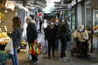 People wearing masks hold bags while shopping at an open-air market in Rome, Thursday, Oct. 22, 2020. Authorities in regions including Italy's three largest cities have imposed curfews in a bid to slow the spread of COVID-19 where it first struck hard in Europe, most of whose countries are now imposing, or mulling, new restrictions to cope with rapidly rising caseloads. (Cecilia Fabiano/LaPresse via AP)