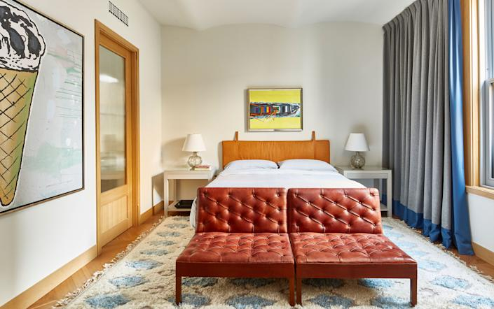 "<div class=""caption""> The guest bedroom is home to leather accents: the antique Danish chairs and the headboard from <a href=""https://www.the-citizenry.com/"" rel=""nofollow noopener"" target=""_blank"" data-ylk=""slk:The Citizenry"" class=""link rapid-noclick-resp"">The Citizenry</a>. The art includes <em>Ice Cream Cone</em> by Donald Baechler and <em>Yellow</em> by Malcolm Morley. The custom curtains feature a blend of fabrics—cashmere from <a href=""https://www.hollandandsherry.com/"" rel=""nofollow noopener"" target=""_blank"" data-ylk=""slk:Holland & Sherry"" class=""link rapid-noclick-resp"">Holland & Sherry</a> and wool from <a href=""https://www.angelabrownltd.com/"" rel=""nofollow noopener"" target=""_blank"" data-ylk=""slk:Angela Brown Ltd."" class=""link rapid-noclick-resp"">Angela Brown Ltd.</a>—and the rug, in alpaca, was sourced from <a href=""https://www.altforliving.com/"" rel=""nofollow noopener"" target=""_blank"" data-ylk=""slk:ALT For Living"" class=""link rapid-noclick-resp"">ALT For Living</a>. </div>"